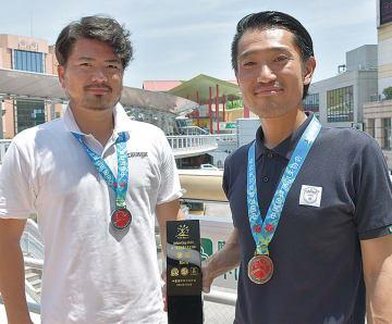 盾を手にする新井さん(右)と和志武さん