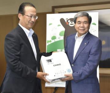 カシオ計算機から寄贈された、光源に水銀を使用しないプロジェクターを受け取る熊本県の蒲島郁夫知事(右)=7日午後、熊本県庁