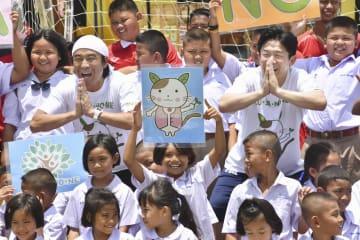 子どもたちと記念撮影するペナルティのワッキーさん(後列左から2人目)とヒデさん(同右から2人目)=7日、タイ中部ラムソムプン(共同)