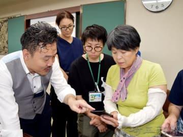 森俊明社長(左)から見守りサービスアプリ「みまサポ2」の説明を聞きながら、スマホのデモ機を操作する参加者ら=2日、横瀬町役場
