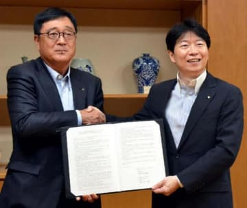 協定を結び、握手する益子修CEO(左)と伊原木隆太知事