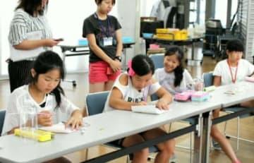 ワークショップで手紙を書く三郷小の児童=中津市山国町のコアやまくに