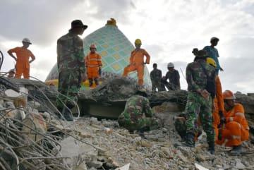インドネシア・ロンボク島の州都マタラム北方の村で、倒壊したモスク周辺を捜索する救助隊=8日(共同)