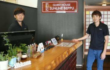 旅館を改装して7月に営業を始めた「ゲストハウス サンライン別府」。南亨支配人(左)は「旅館、ゲストハウスを融合した魅力を提供したい」と話す=北浜