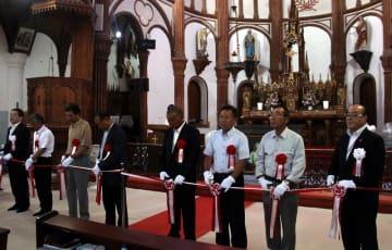 黒島天主堂の祭壇前でテープカットをして絵画展の開幕を祝う地元関係者ら=佐世保市