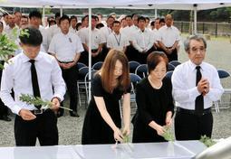 防災を誓うモニュメントに花を手向ける参列者=9日午前、兵庫県佐用町久崎、復興ひろば