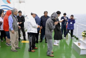 北方領土・国後島沖の船上での慰霊式で、手を合わせる墓参団員ら=9日午前(同行記者団撮影)