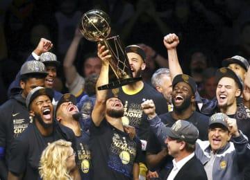 6月、NBAで2連覇を果たし、トロフィーを掲げて喜ぶウォリアーズの選手たち(ゲッティ=共同)