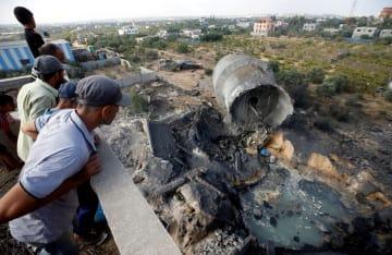 イスラエル軍による空爆被害を見る人々=9日、パレスチナ自治区ガザ近郊(ロイター=共同)