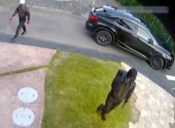 愛知県警が公開した、黒ずくめの男が県内の住宅に侵入しようとする様子が写った防犯カメラ映像