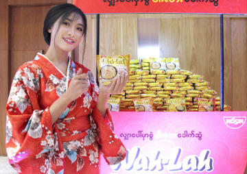 日清食品HDの合弁会社がミャンマーで発売した即席麺「ワー・ラー」をPRする女性=9日、ヤンゴン(共同)