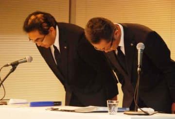 記者会見で頭を下げる菖蒲田取締役専務執行役員(右)と向井武司常務執行役員