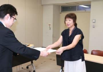 県の担当者に要望書を手渡す「県私学の公費助成をすすめる会」の中村直美会長(右)=9日、県庁