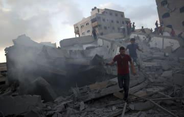 9日、パレスチナ自治区ガザで、イスラエル軍の空爆により損壊した建物を見て回る市民ら(AP=共同)