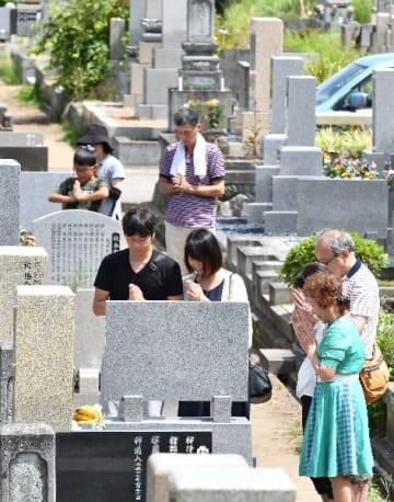 お盆には家族連れが墓に手を合わせ先祖をしのぶ