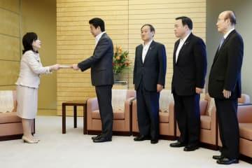 人事院の一宮なほみ総裁(左端)から人事院勧告を受け取る安倍首相(左から2人目)ら=10日午前、首相官邸