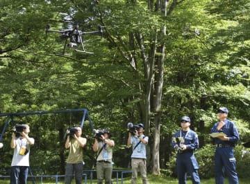 栃木県日光市の憾満ケ淵周辺で、行方不明になっているフランス人女性をドローン(左上)を投入し捜索する栃木県警の捜査員ら(右端の2人)=10日午前