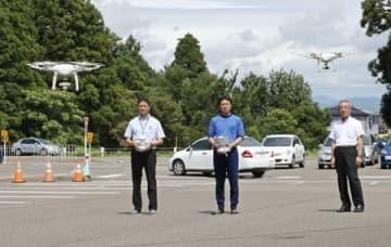ドローンを操縦する上越自動車学校の教習指導員ら=9日、上越市