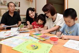 瓜谷幸孝さん(左端)らの呼び掛けに応じ、「元気メール」をしたためる子どもたち=神戸市垂水区