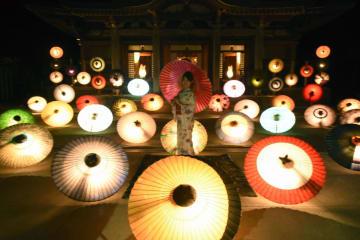 「大山の大献灯」が始まり、ライトアップされた色とりどりの和傘=10日夜、鳥取県大山町の大山寺