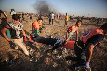 10日、パレスチナ自治区ガザのイスラエルとの境界で、負傷したデモ参加者を運ぶパレスチナ人(ゲッティ=共同)
