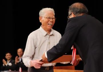 世界文化遺産登録記念式典で江上町長から感謝状を贈られる松井さん(左)=新上五島町石油備蓄記念会館