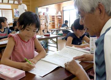 アドバイスを受けながら宿題に取り組む児童=佐世保市小佐々町、黒石地区公民館