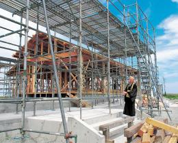 ようやく再建にこぎ着けた本堂の建設現場に立ち、被災から7年5カ月の苦労を振り返る早坂さん=2日、宮城県山元町