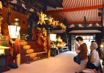 多くの灯籠に照らし出された「石の間」で手を合わせる参拝者(京都市上京区・北野天満宮)