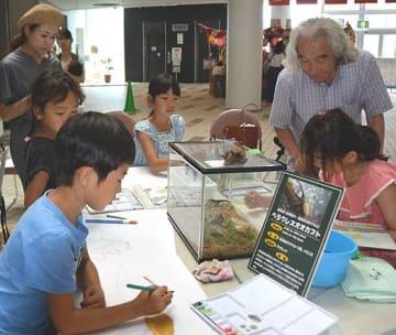 加藤会長(右奥)の指導でカブトムシやクワガタムシの水彩画に取り組む子どもたち=10日、境港市の夢みなとタワー
