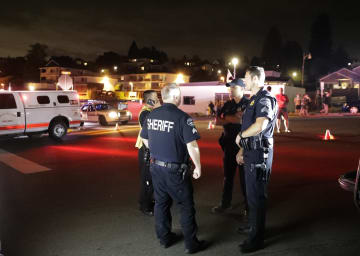 民間機が墜落した現場近くの港で警戒する当局者ら=10日、米西部ワシントン州(AP=共同)