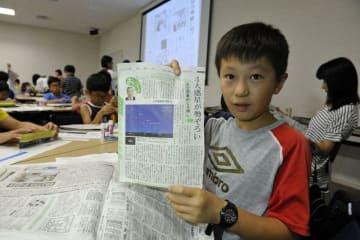 科学や環境を学ぶワークショップで、天文観測の記事を示す男子児童=日本新聞博物館