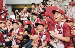 ピッチで練習を見学し、イニエスタ選手の登場に目を輝かせる子どもたち=ノエビアスタジアム神戸