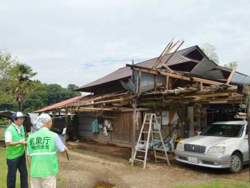 屋根が破損した納屋を調査する宇都宮地方気象台の職員=11日午前10時35分、那須烏山市森田(画像は一部加工しています)