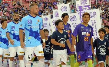 原爆が投下された日を意味する「86」と「89」のユニホームで入場する両チームの選手ら=広島市、エディオンスタジアム広島