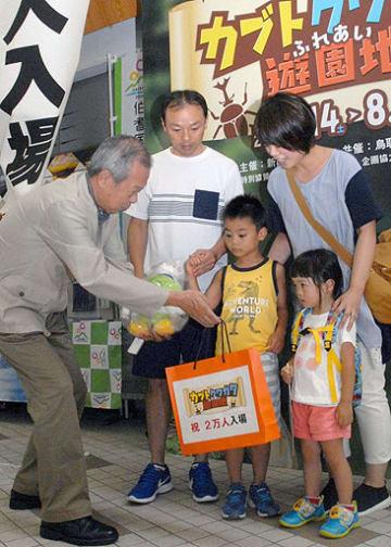 衣笠理事長(左)から記念品を手渡される山根さん家族=11日、境港市の夢みなとタワー