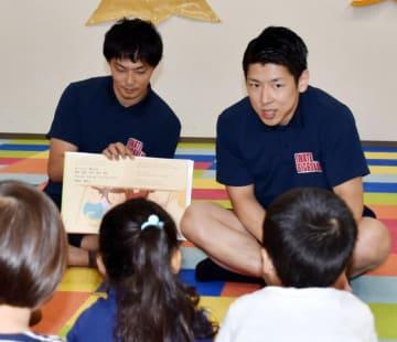 絵本の読み聞かせをする千葉慎也選手(右)と枡田祐介選手
