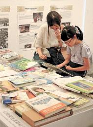 広島の原爆をテーマにした絵本を大人と一緒に読む子ども
