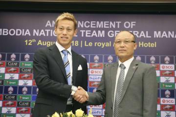 カンボジア・サッカー協会会長(右)と握手する本田圭佑選手=12日、プノンペン(NNA=共同)