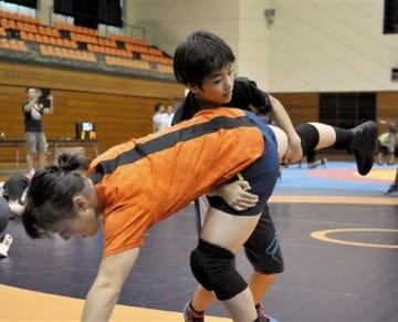 レスリング教室で登坂絵莉選手(左)を相手にタックルを仕掛ける参加者=熊本市総合体育館