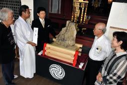 234年ぶりに姫路に戻った珪化木を囲む幸田精久宮司(左から2人目)や山下博文会長(中央)ら=広峯神社
