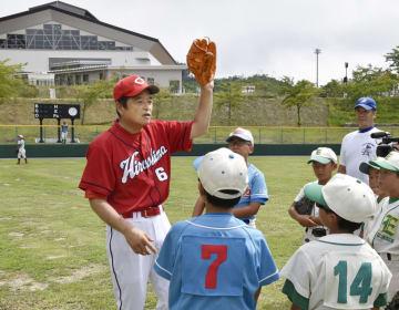 福島県飯舘村にオープンした「いいたてスポーツ公園」で、小中学生に野球の指導をする元広島の小早川毅彦さん=12日午後