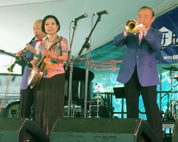 音楽フェスで演奏する外山喜雄さん(右)と妻の恵子さん(手前左)=4日、米ニューオリンズ(AP=共同)