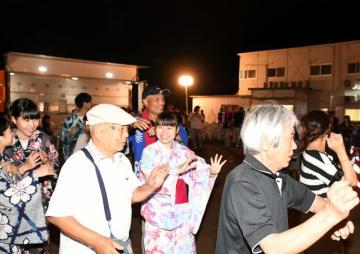 約30年ぶりに復活した盆踊りを楽しむ地域住民と大学生ら=11日午後7時15分、宮古市腹帯