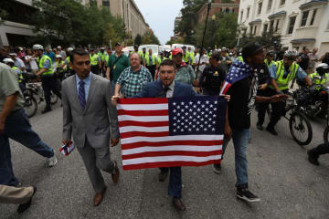 白人至上主義者の集会で、行進する活動家ジェイソン・ケスラー氏(中央)ら=12日、ワシントン(ロイター=共同)