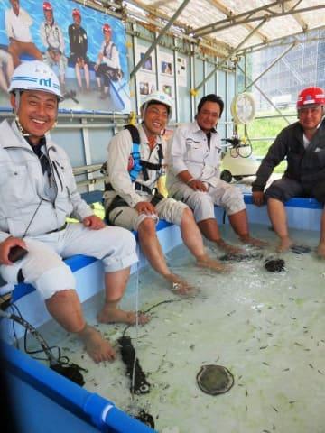 休憩のひととき、ドクターフィッシュが泳ぐ水槽に足を浸して涼む作業員ら=横須賀市長坂