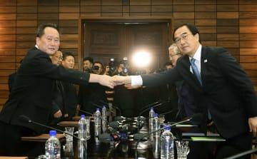 13日、板門店の北朝鮮側施設「統一閣」で開かれた南北閣僚級会談で、握手する韓国の趙明均統一相(右)と、北朝鮮の李善権・祖国平和統一委員会委員長(聯合=共同)