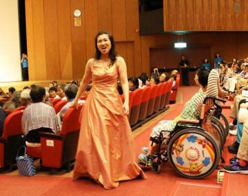ステージから客席に降りて歌声を聞かせる松永さん(中央)=横須賀市文化会館