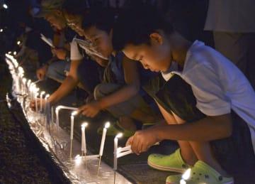 高野山奥の院の参道で、ろうそくに火をともす子ども=13日夜、和歌山県高野町