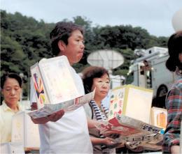 安全な社会の実現を願うメッセージを記した灯籠を手にする孝行さん、弘美さん夫妻(中央)=11日午後6時50分ごろ、群馬県上野村